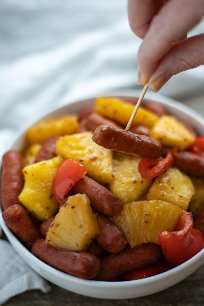 Woman's hand using a toothpick to grab a sausage from a bowl of Hawaiian Lit'l Smokies (vertical)