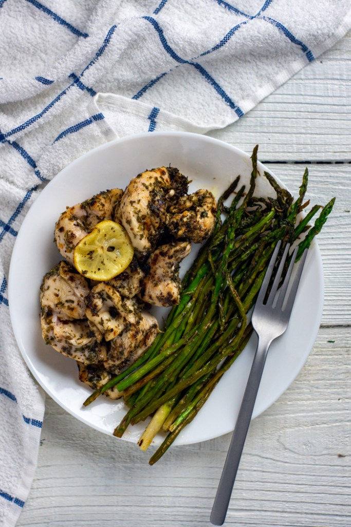 Lemon-herb chicken kabobs next to cooked asparagus with a stainless steel fork on a round white plate with a white and blue towel behind all on a white wooden surface (vertical)