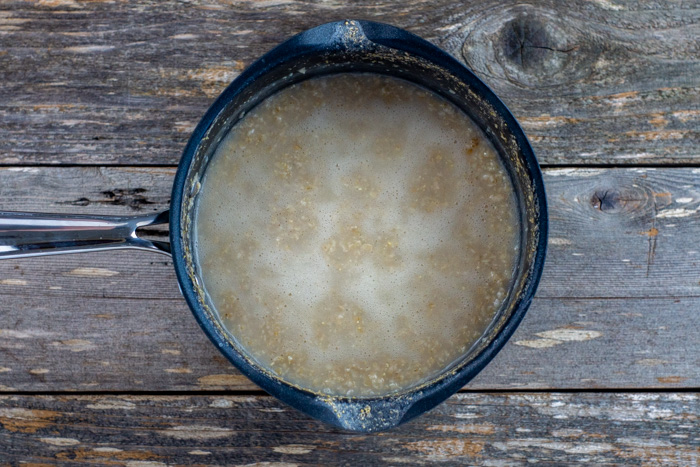 Oats boiling in water in a saucepan on a wooden surface