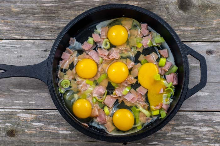 Diced ham and leeks with eggs in a cast iron skillet on a wooden surface