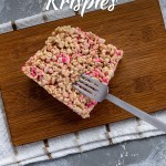 Square piece of sprinkled rice krispies on a bamboo platter with a stainless steel fork on a white and brown towel all on a grey and white surface (with title overlay)