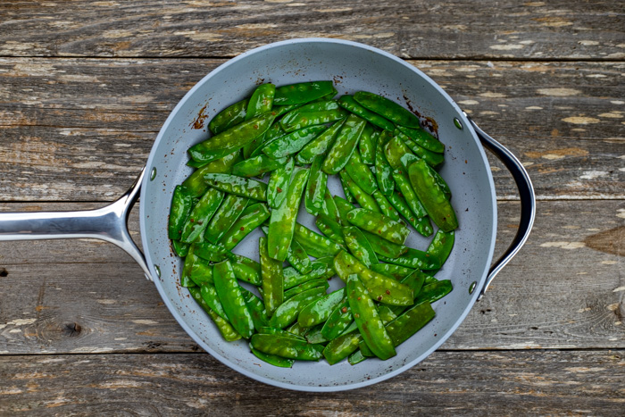 Toasted snow peas in a skillet on a wooden surface
