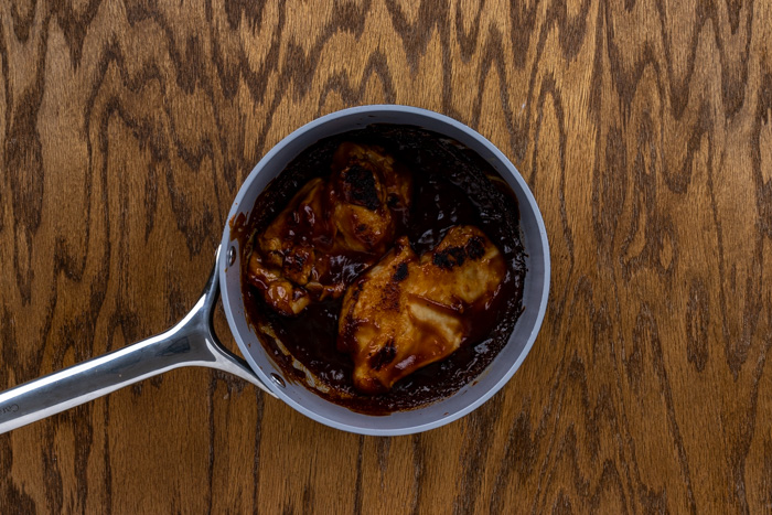Chicken in bbq sauce in a saucepan on a wooden surface