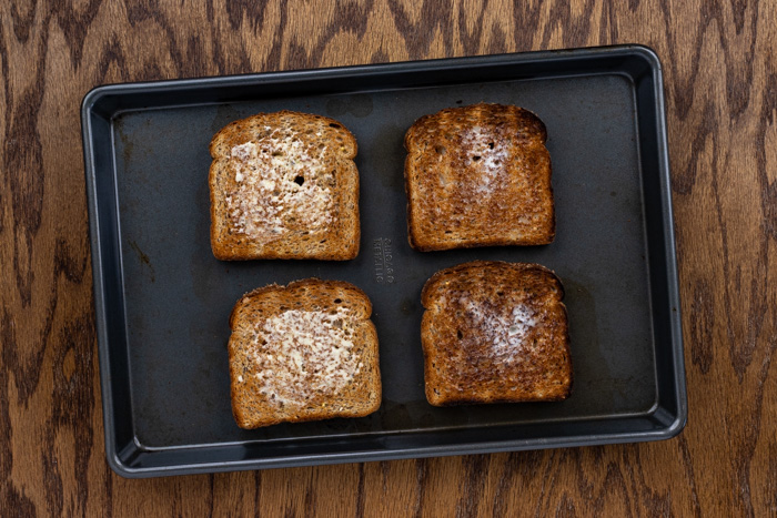 Toasted bread with butter on a baking sheet on a wooden surface