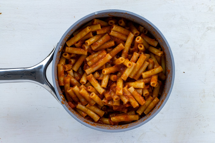 Cooked ziti noodles with pasta sauce in a saucepan on a white wooden surface