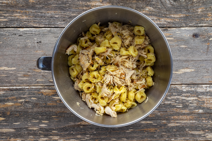 Shredded cooked chicken with cooked tortellini and lemon dressing in a stainless steel bowl on a wooden surface