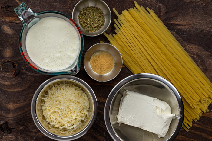 Ingredients for fettuccine alfredo in stainless steel bowls on a wooden surface