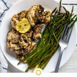 Lemon-herb chicken kabobs next to cooked asparagus with a stainless steel fork on a round white plate with a white and blue towel behind all on a white wooden surface (with logo overlay)