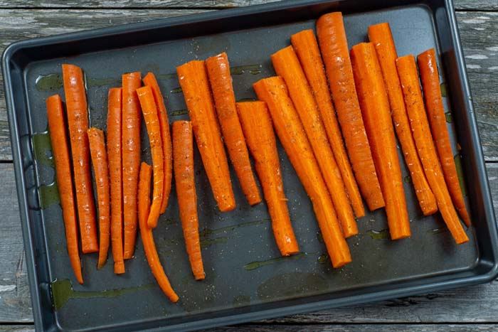 Sliced carrots drizzled with olive oil on a baking sheet on a wooden surface