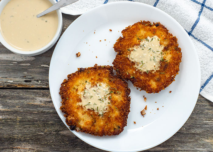 Two salmon cakes topped with buttermilk sauce on a round white plate with a bowl of buttermilk sauce and a white and blue towel behind all on a wooden surface