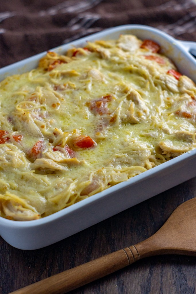 Spaghetti casserole with chicken and cheese in a white casserole dish next to a wooden spoon with a brown towel behind all on a wooden surface (vertical)