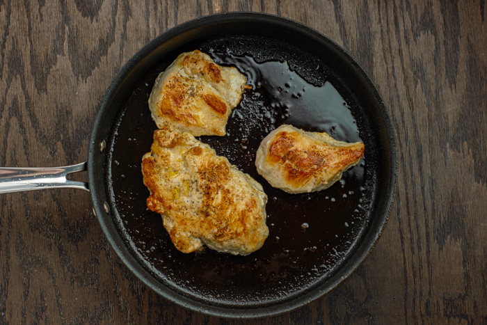Breaded chicken in a skillet on a wooden surface