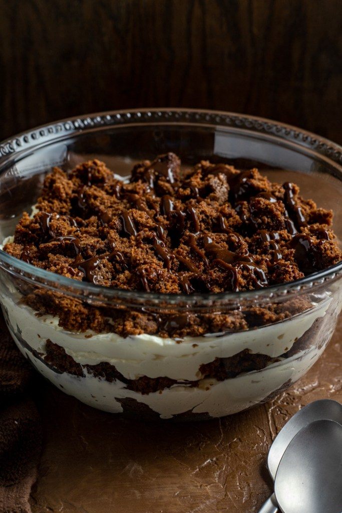 Brownie cheesecake trifle drizzled with hot fudge topping in a glass trifle bowl next to a stainless steel spoon on a wooden surface (vertical)