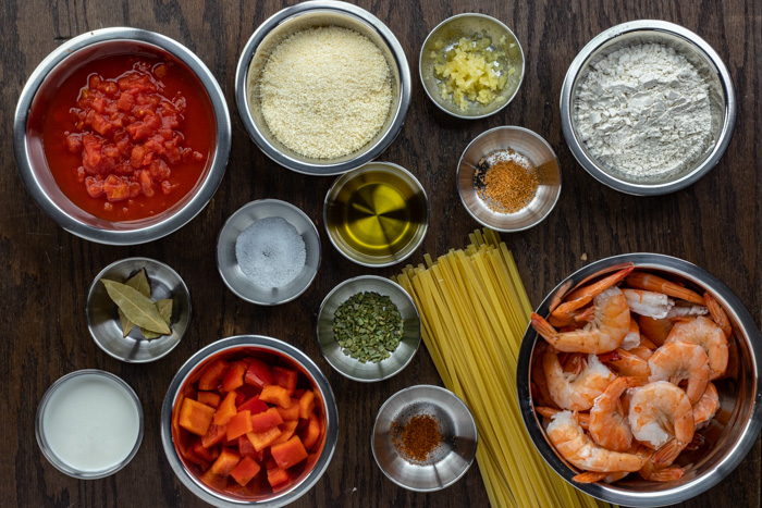 Ingredients for creamy shrimp pasta in stainless steel bowls on a wooden surface