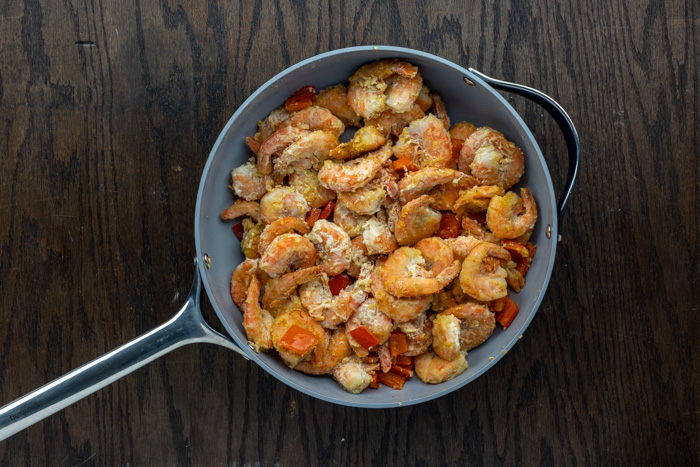 Cooked red pepper and coated shrimp in a skillet on a dark wooden surface