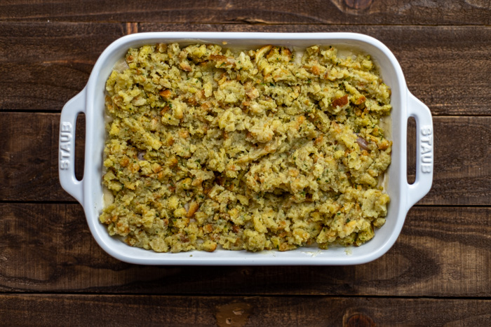 Casserole dish with stuffing on top on a wooden surface
