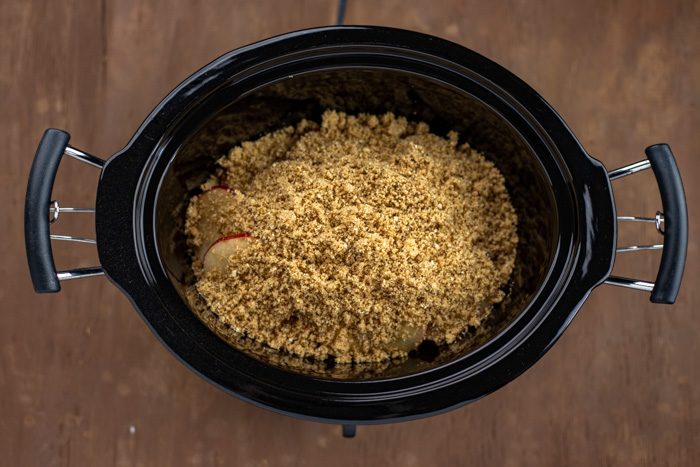Apples and crumble mixture layered in a slow cooker on a wooden surface