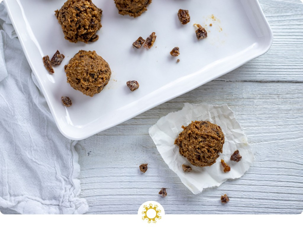 Almond-Date energy ball on a piece of parchment paper with a tray of energy balls behind all on a white wooden surface (with logo overlay)