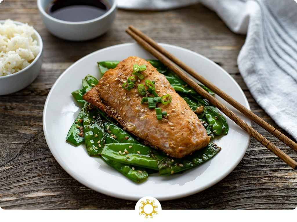 Orange ginger salmon topped with sliced green onion with toasted snow peas and wooden chopsticks on a round white place with a bowl of white rice and orange-ginger sauce behind next to a white towel all on a wooden surface (with logo overlay)