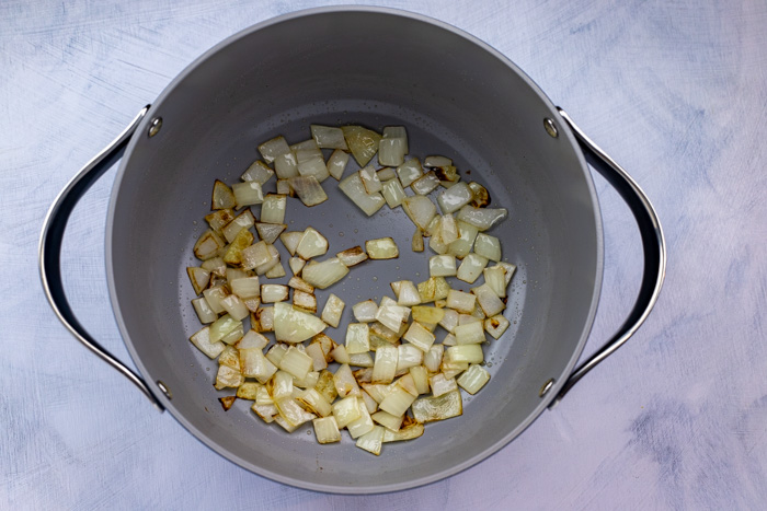 Diced onion in a large pot on a white and blue surface