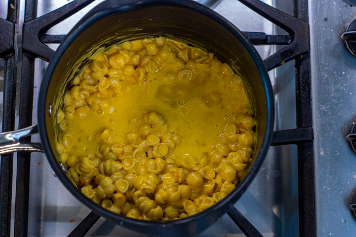 Mac and cheese mixed with pumpkin and egg in a pot on a gas stovetop