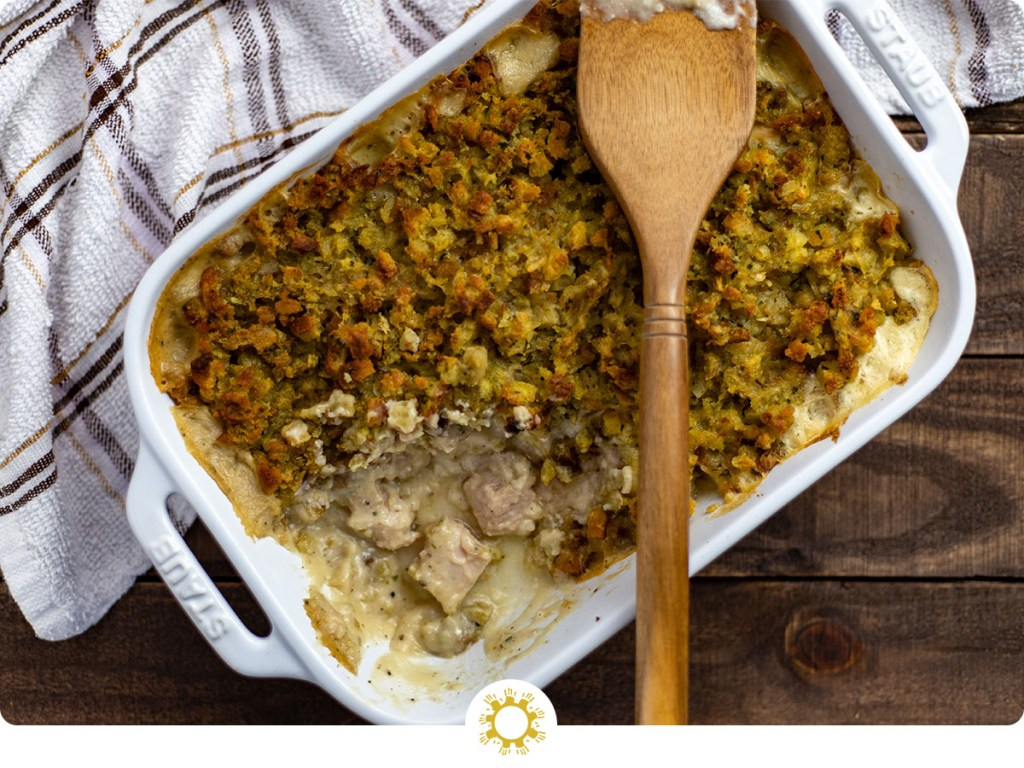 Easy chicken casserole with a wooden spoon in a white casserole dish with a white and brown towel behind all on a wooden surface (with logo overlay)