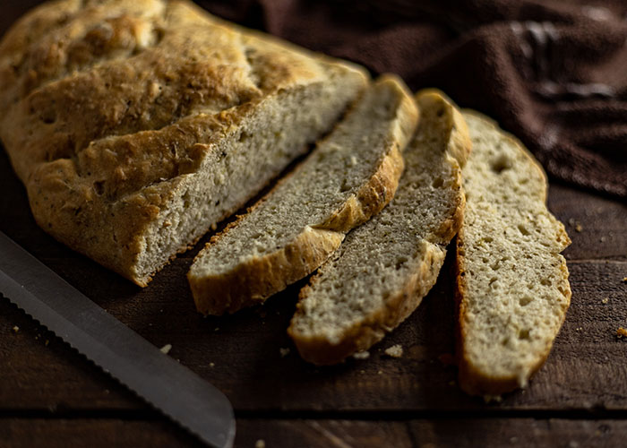 Sliced herbed tuscan bread next to a bread knife with a brown towel all on a wooden surface