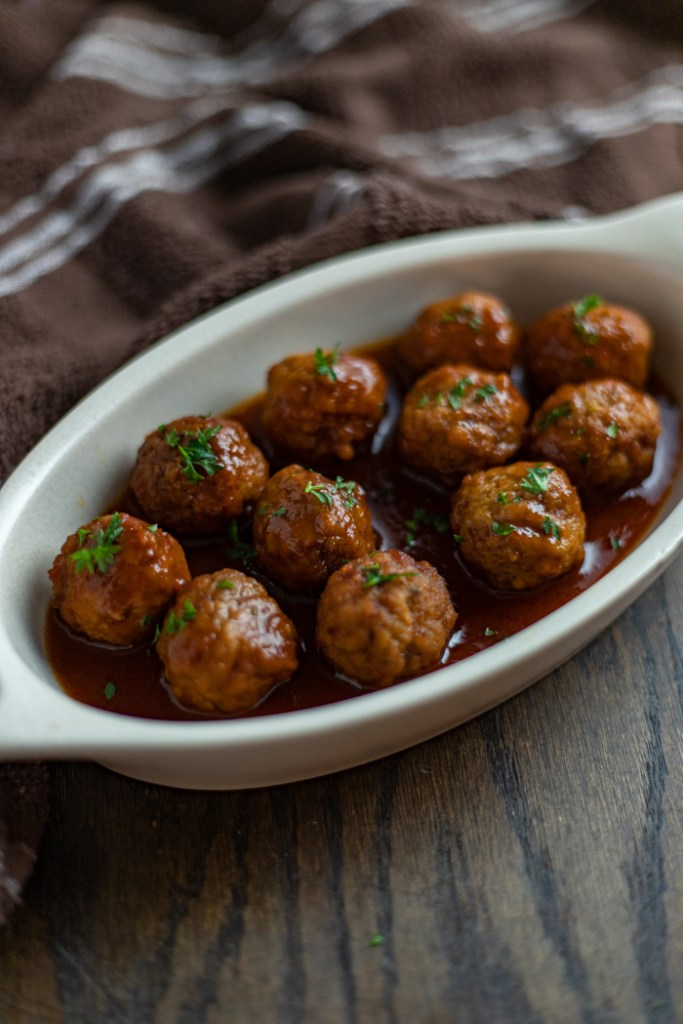 Slow cooker Swedish meatballs garnished with parsley in a white oval dish with a brown and white towel behind all on a brown wooden surface (vertical)