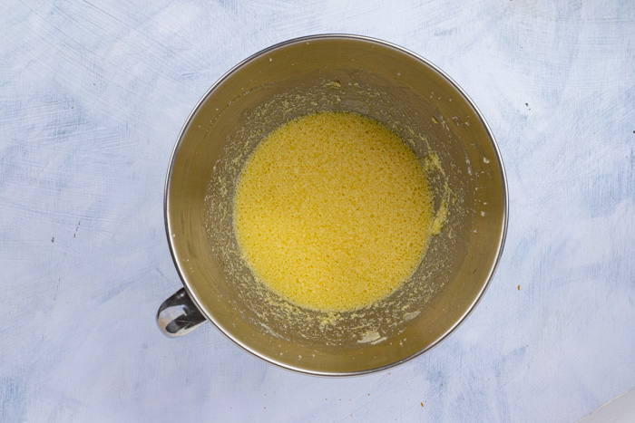 Creamed butter and sugar with eggs in a stainless steel bowl on a white surface