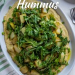 Salad with warm potatoes and hummus with arugula on a white oval serving tray with a white and green towel all on a white surface (with title overlay)