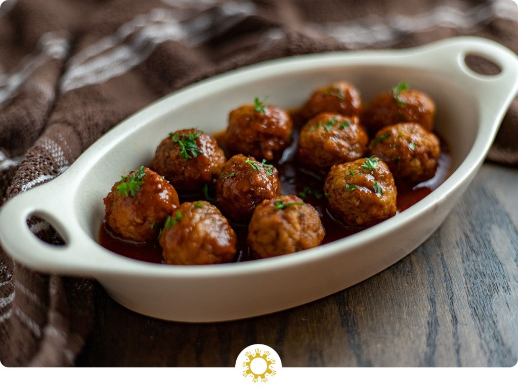 Slow cooker Swedish meatballs garnished with parsley in a white oval dish with a brown and white towel behind all on a brown wooden surface (with logo overlay)