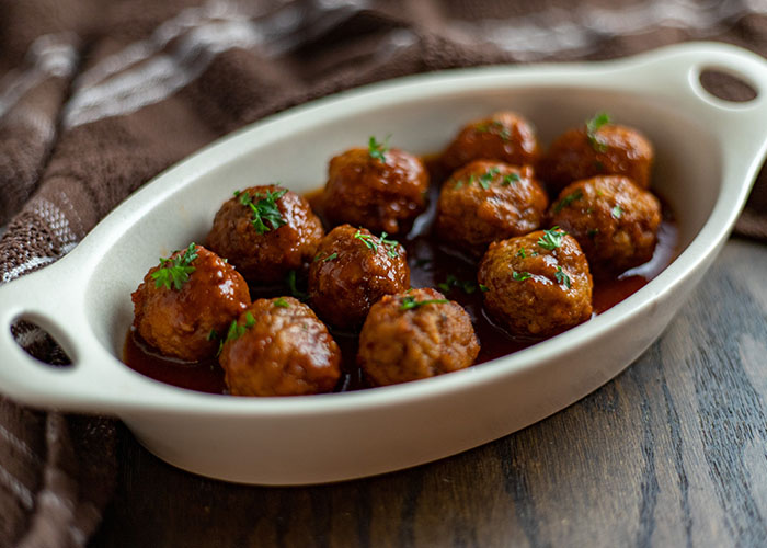 Slow cooker Swedish meatballs garnished with parsley in a white oval dish with a brown and white towel behind all on a brown wooden surface