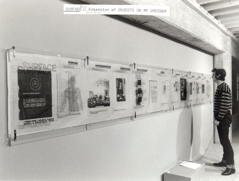 """Surface (wall hanging scroll),"" installation view, vinyl lettering on printed acetate, and photocopy and colored pencil on paper, 24"" x 213 ½"", displayed at Media Gallery, San Jose, 1987 Photograph copyright Martin Cox."
