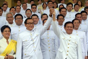 Cambodian opposition leader Sam Rainsy (C-L) raises hands with Kem Sokha (C-R), deputy of Cambodia National Rescue Party (CNRP) in front of members of parliament before the swearing in ceremony inside the Royal Palace in Phnom Penh on August 5, 2014. Rainsy and 54 other members of his party were sworn in as members of parliament on August 5, after a year-long boycott of parliament triggered by a disputed election. AFP PHOTO/ TANG CHHIN SOTHY / AFP PHOTO / TANG CHHIN SOTHY