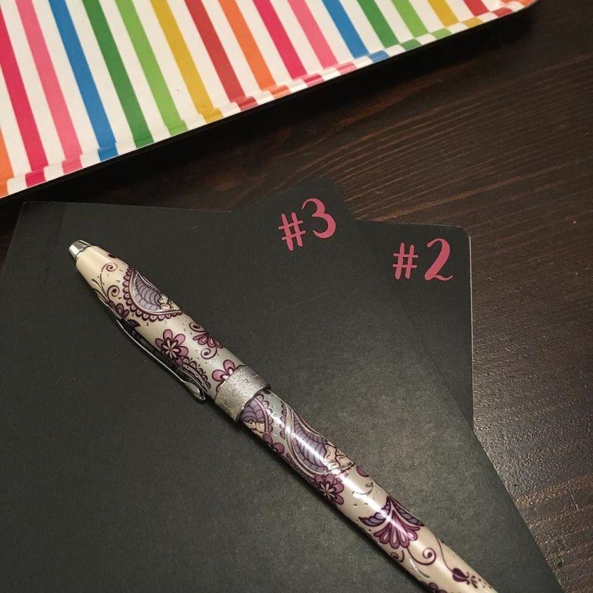 2 cahiers, un stylo plume et un plateau aux couleurs de l'arc en ciel
