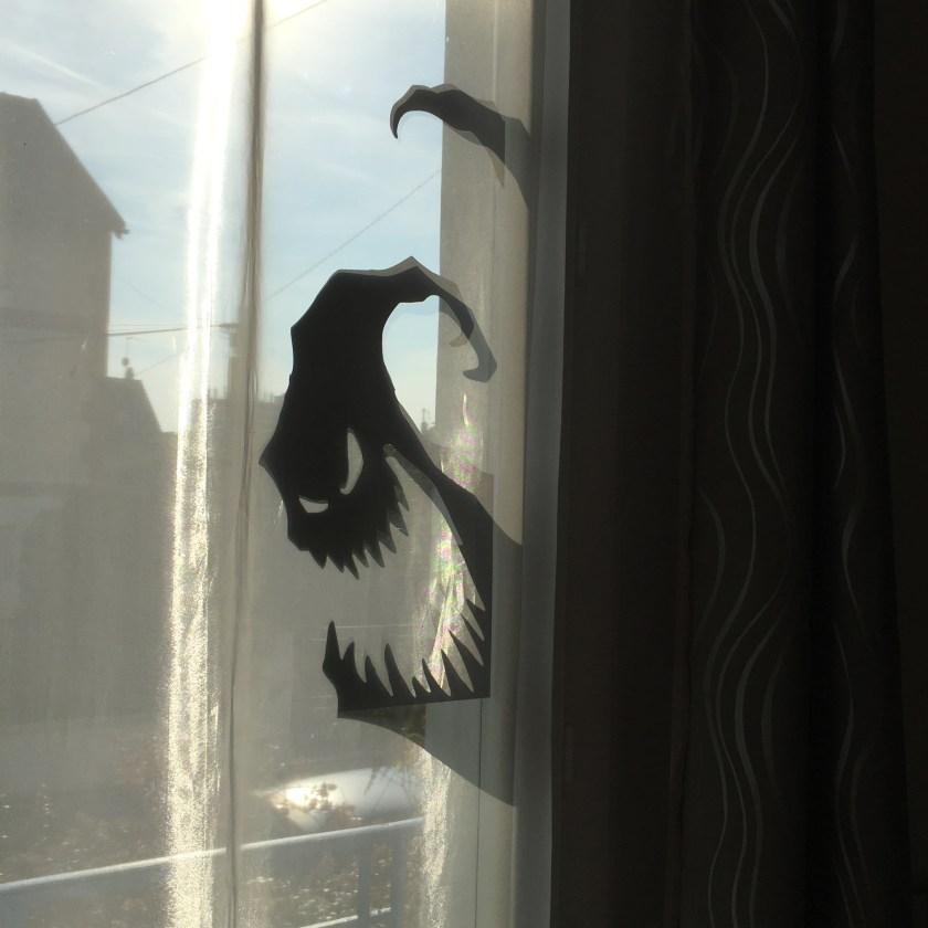 Sticker représentant un fantôme avec la gueule ouverte et un air sardonique collé sur une vitre de fenêtre