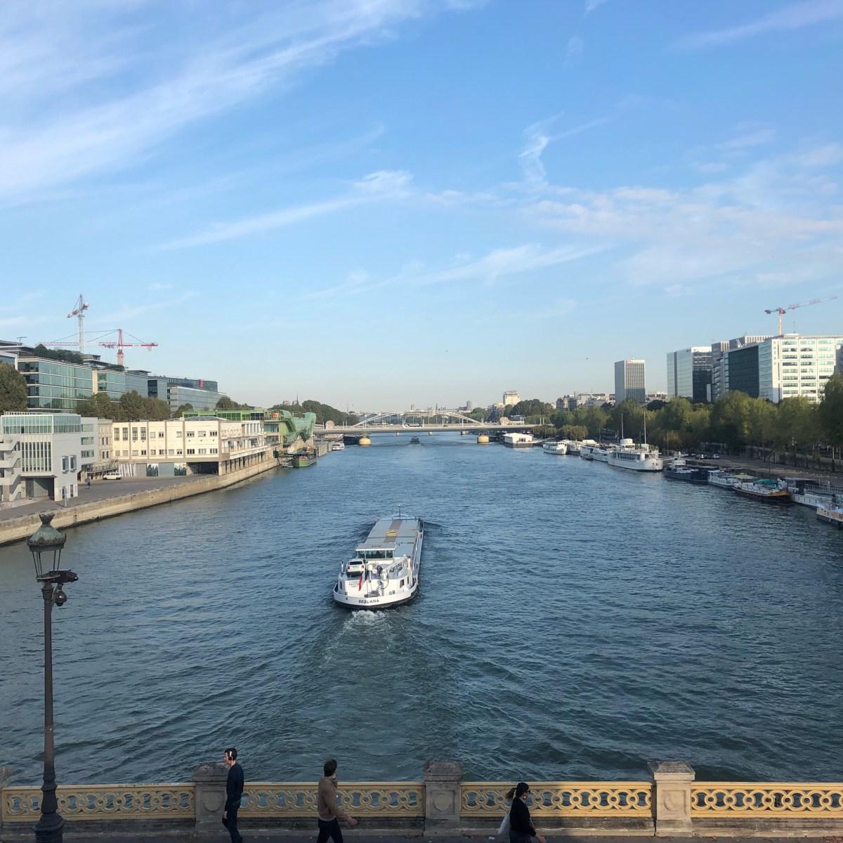 Vue du pont de Bercy, une péniche sur la Seine, un ciel bleu parsemé de nuages.