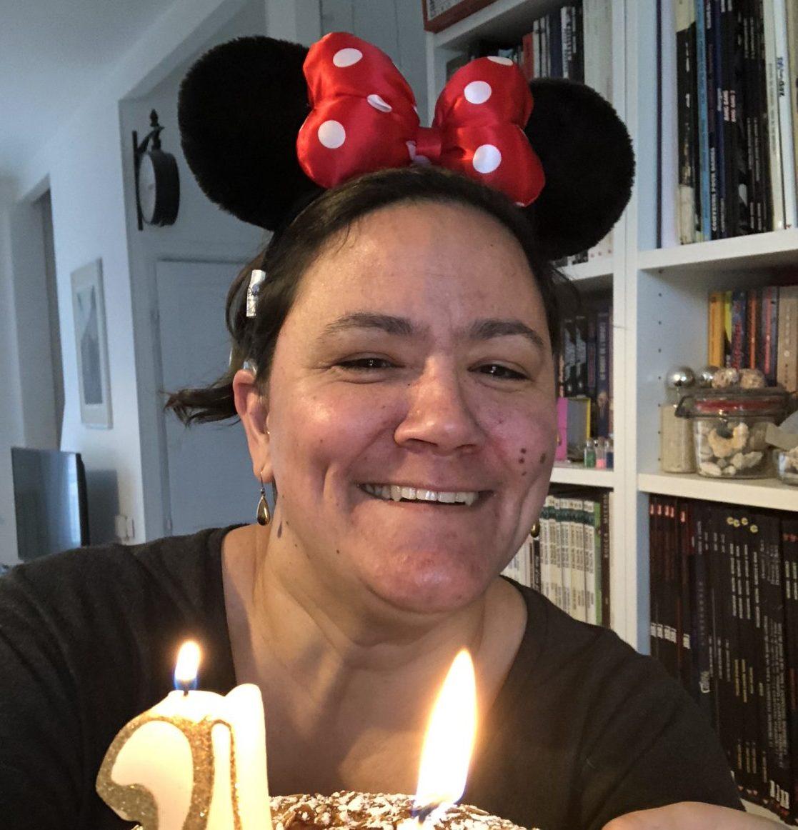Sophie avec des oreilles de minnie et un gâteau portant des bougies dessus