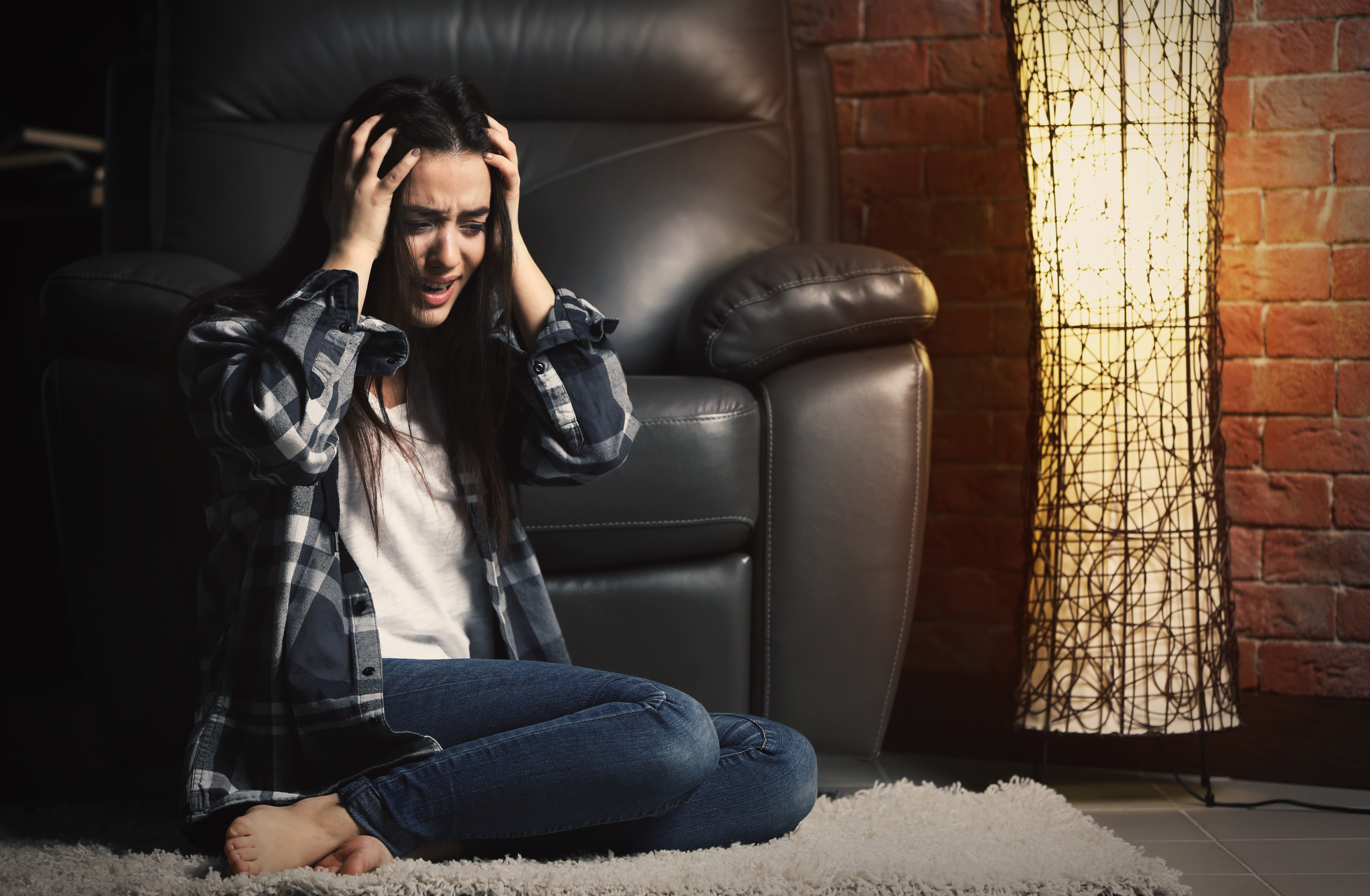 Depressed woman sitting near leather armchair indoors