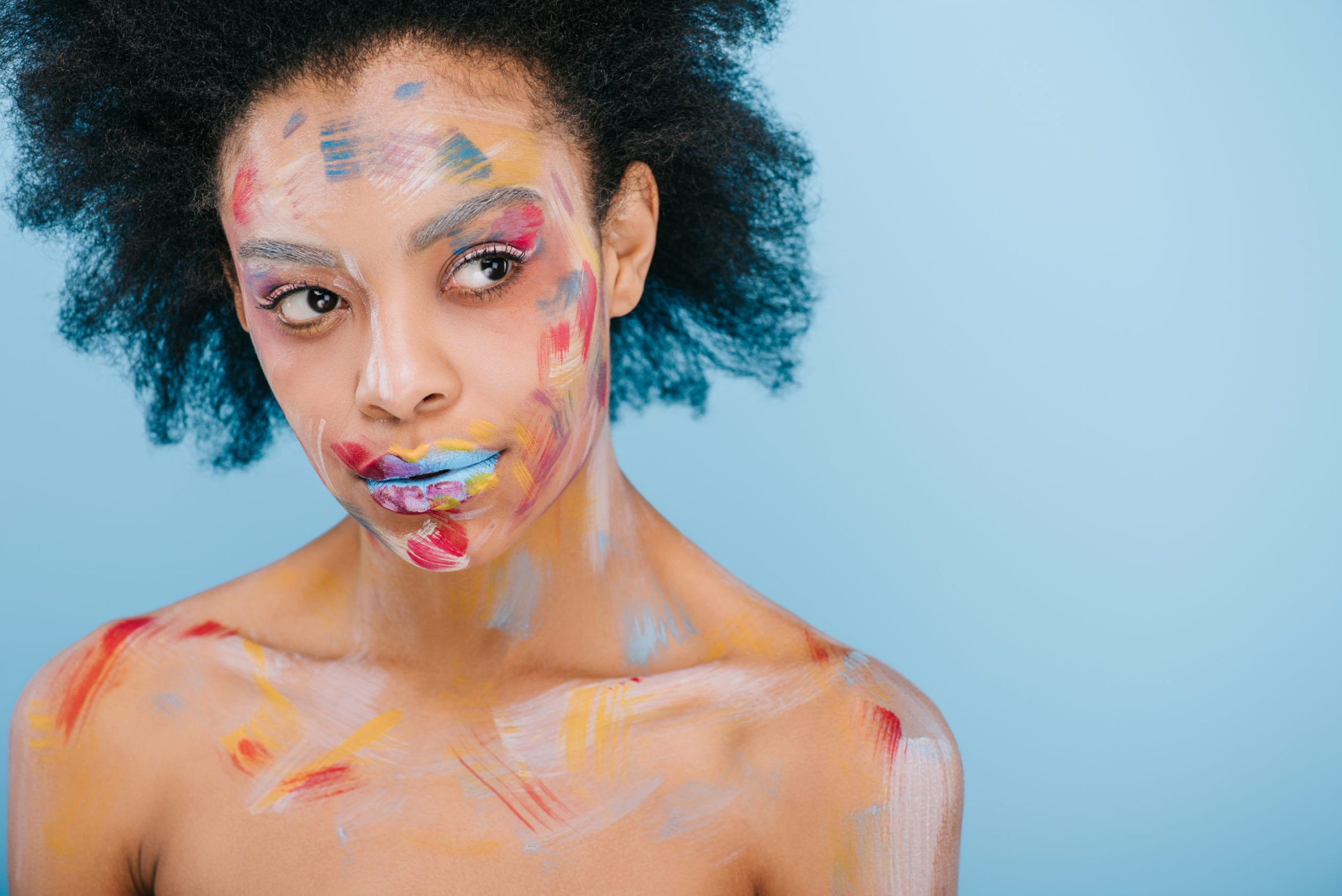 attractive young woman with paint strokes on face looking away isolated on blue