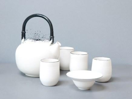Service à thé, théière blanche en porcelaine liseré noir, broderie gris carbone, gobelets porcelaine liseré noir et coupelle avec liseré noir.