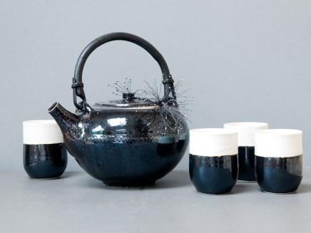 Service à thé, grande théière, 15 cm x 21 cm, émail 'gouttes d'huile', natte brodée, et 6 gobelets en porcelaine noir et blanc, 10 x 7,5 cm.