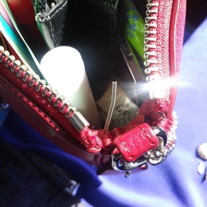 Red pebbled Coach Nolita 19 wristlet bag with a defect.