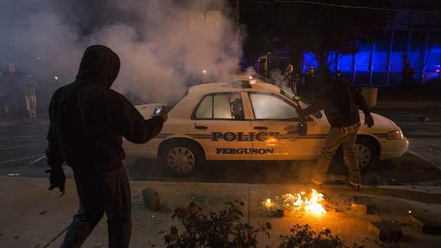 Men photograph a burning police vehicle after it was damaged and set ablaze by protesters outside of City Hall in Ferguson