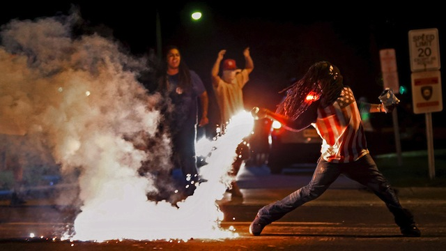 Edward Crawford returns a tear gas canister fired by police  who were trying to disperse protesters in Fergusons