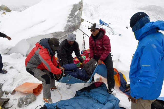 In this photograph taken on April 25, 2015, rescuers help a porter onto a makeshift stretcher after he was injured by an avalanche caused by an earthquake, before being evacuated to a medical tent in another area of Everest Base Camp.   Rescuers in Nepal are searching frantically for survivors of a huge quake on April 25, that killed nearly 2,000, digging through rubble in the devastated capital Kathmandu and airlifting victims of an avalanche at Everest base camp.   AFP PHOTO/Roberto SCHMIDTROBERTO SCHMIDT/AFP/Getty Images