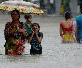 personas caminando con el agua a la altura de la cadera por la inundaciones en India