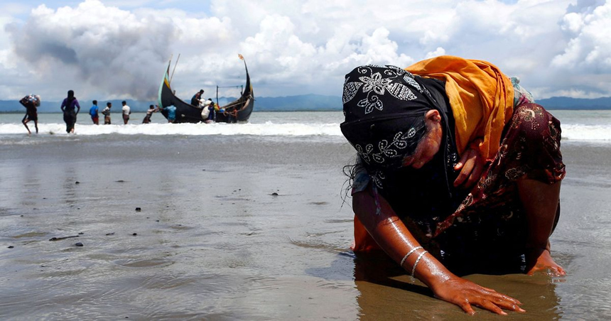 mujer refugiada rohingya agotada toca la orilla luego de cruzar la frontera entre Bangladesh