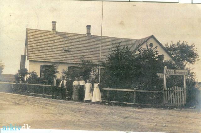 Billedet er et fotografi i brunlige nuancer af huset på adressen Svinget 3. Foran står syv herrer og damer i deres pæne tøj. Over indgangen hænger et skilt med teksten Afholds-Restauration.