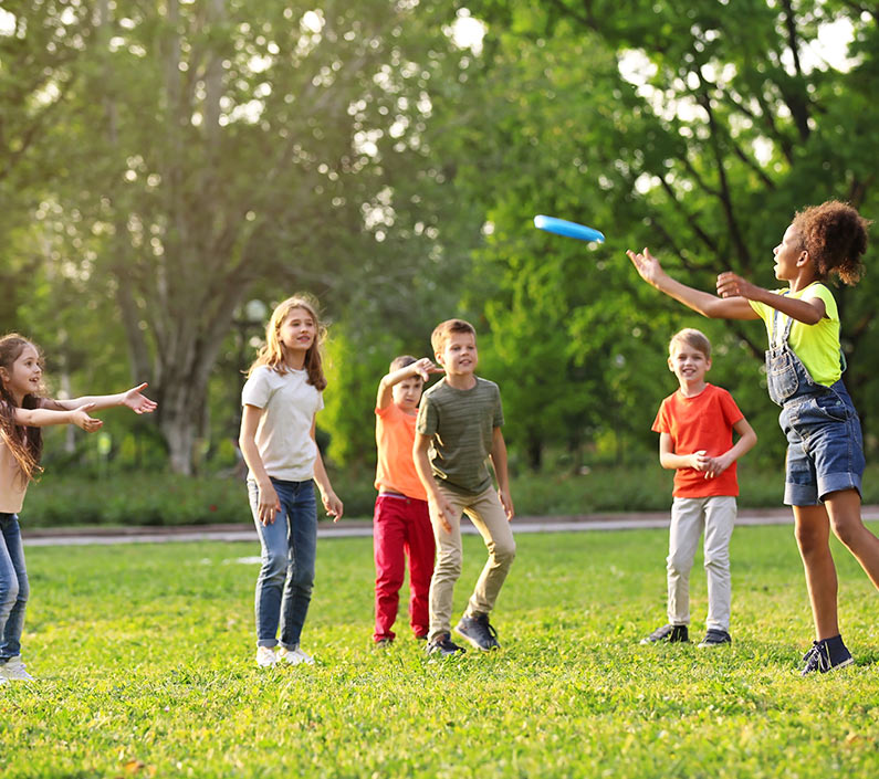 Children playing Frisbee in park